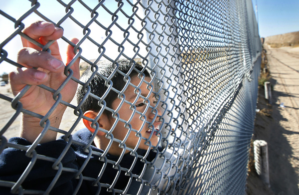 Young Mexican boy watches Border Patrol on New Mexico side of border fence